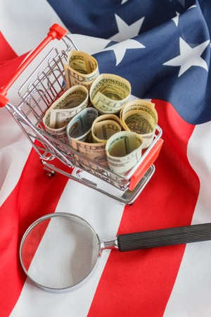 Shopping cart and Magnifying glass on the national flag of United States of America, soft focus background
