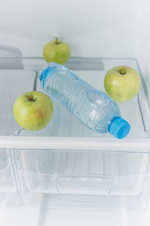 Empty refrigerator with a bottle of water and green apples on the shelf, diet concept, blurred background Stok Fotoğraf