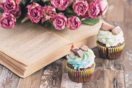 Handmade chocolate muffins with decorations. Book and a bouquet of roses, soft focus background