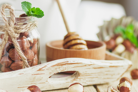 Honey in the wooden bowl, mint leaves, hazelnuts and jar with milk on the wooden tray, soft focus background Stok Fotoğraf