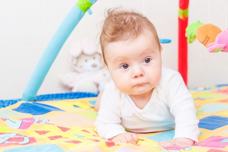 Playing little child on the colored mat for developing, blurred background Stok Fotoğraf
