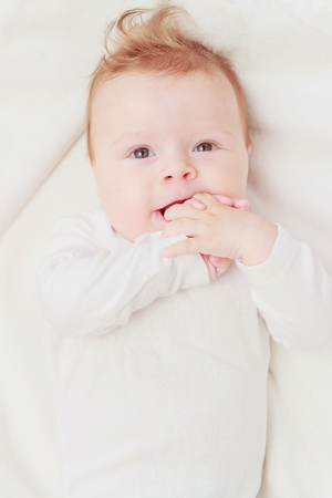 Happy child on the white blanket, blurred background, top view