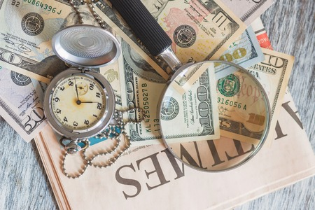Pocket clock, American dollars and a magnifying glass, soft focus background Stok Fotoğraf
