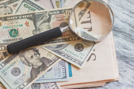 Newspaper, American dollars and a magnifying glass, soft focus background