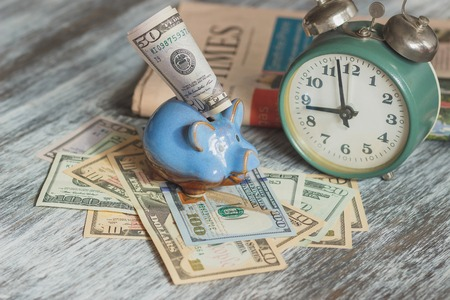 Piggy bank, alarm clock and American dollars, soft focus background