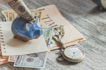 Piggy bank with American dollars and a pocket watch, soft focus background