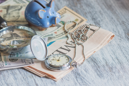 Piggy bank with American dollars and a magnifying glass, soft focus background