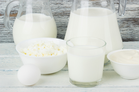 Different dairy products on the white wooden boards, blurred background