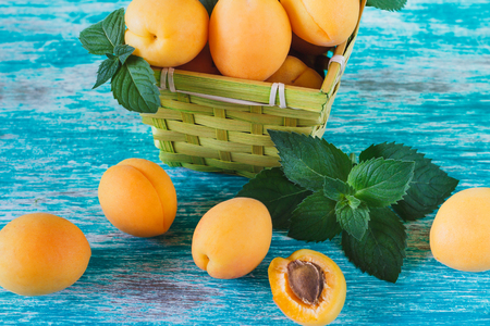 Ripe orange apricots in the basket with leaves of mint and glass of juice, light blue background Stok Fotoğraf