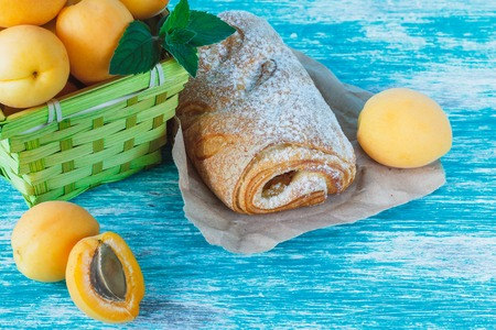 Ripe orange apricots in the basket with leaves of mint and baked goods on the parchment paper, light blue background