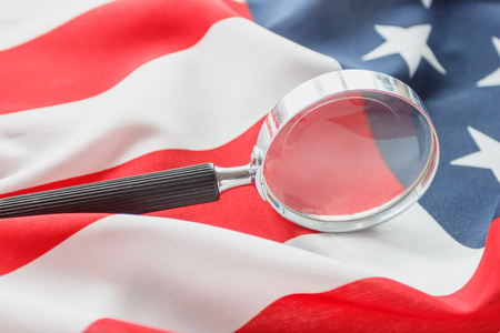 Magnifying glass on the national flag of United States of America, soft focus background