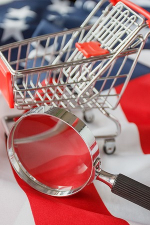 Magnifying glass and a shopping cart on the national flag of United States of America, soft focus background Stok Fotoğraf