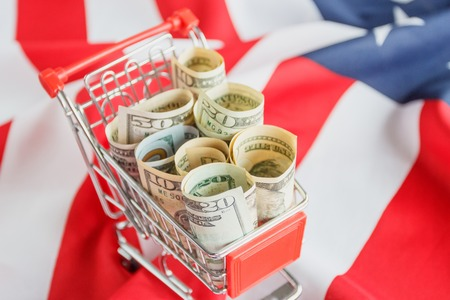 Shopping cart with American dollars inside on the national flag of United States of America, soft focus background Stok Fotoğraf