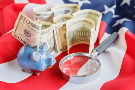 Magnifying glass and American dollars on the national flag of United States of America, background, top view