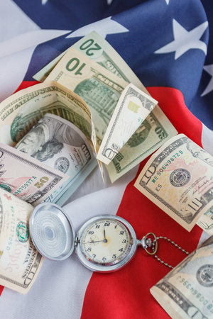 Pocket watch and American dollars on the national flag of United States of America, soft focus background
