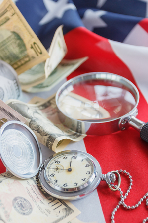 Pocket watch, Magnifying glass and American dollars on the national flag of United States of America, soft focus background