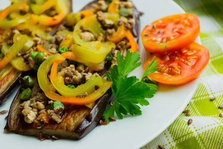 Fried eggplants with minced meat and different vegetables, flaxseed decoration, finished dish, soft focus background