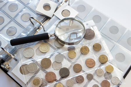Diferentes monedas antiguas de coleccionista con lupa, enfoque suave