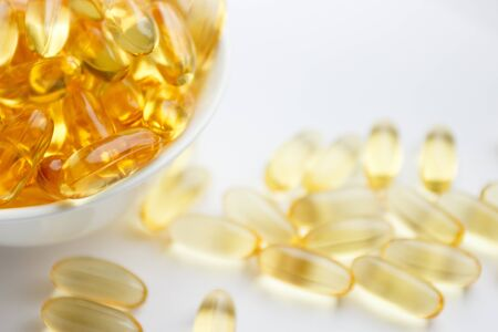 Dietary supplementation. Capsules of fish oil in the white bowl on the light background