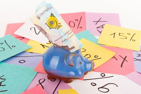 one thousand hryvnias, piggy bank, stickers with financial signs and symbols, light background
