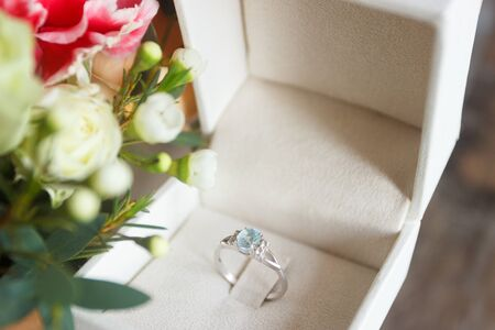 Silver ring and a bouquet of flowers, soft focus background