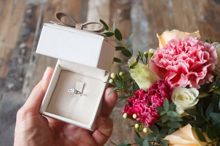 Silver ring in the hand and a bouquet of flowers, soft focus background