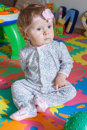Playing little child on the colored mat for developing, soft focus background