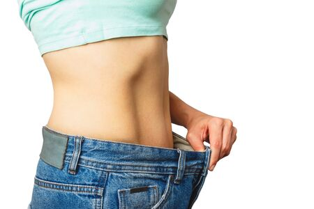 Slim beautiful woman wears jeans large size, diet and health concept, isolated
