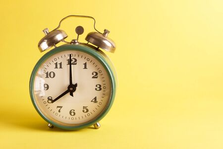 Green alarm clock on the saturated yellow background