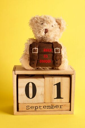 Brown teddy bear with school backpack and decoratibe wooden calendar, saturated yellow background Stok Fotoğraf