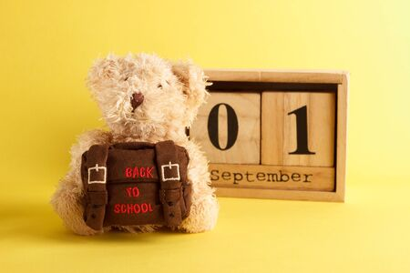 Brown teddy bear with school backpack and decoratibe wooden calendar, saturated yellow background