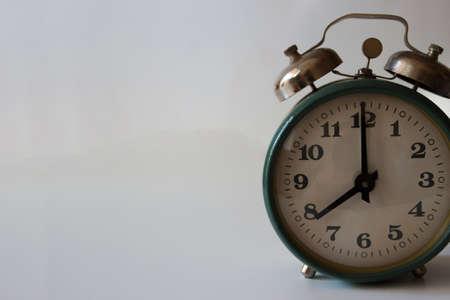 Green alarm clock on the light gray background, close up Reklamní fotografie