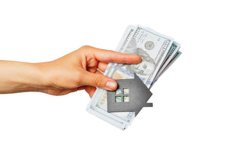 Banknotes of hundred dollars with a house symbol and colored stickers in the hand, soft focus background