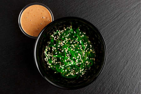 Chuka salad from seaweed, sesame and thick creamy dressing, background from black slate stone, top view