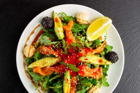 Japanese food: Salad from salmon, arugula, seaweed and sesame, top view