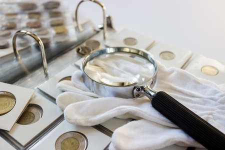 Different old collector's coins with a pair of gloves, soft focus background