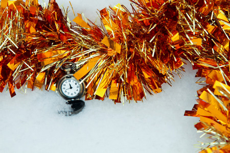tinsel with a clock in the snow