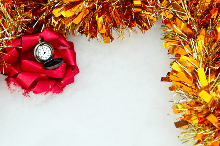 big red bow with a clock in the snow with tinsel