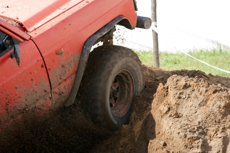 mud pit: offroad car trying to come out from a pit