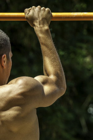 muscular arm of a man doing excercise on the street\ Unrecognizable