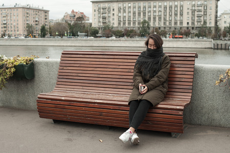 Girl sitting on the bench on the bank of Moskva-river