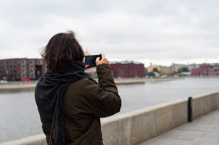 red hair girl: Girl taking picture with the phone on the bank of Moscow-river Stock Photo
