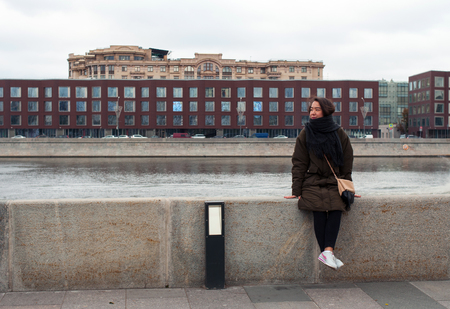 far away look: Girl on the bank of Moskva-river in Moscow of Russia