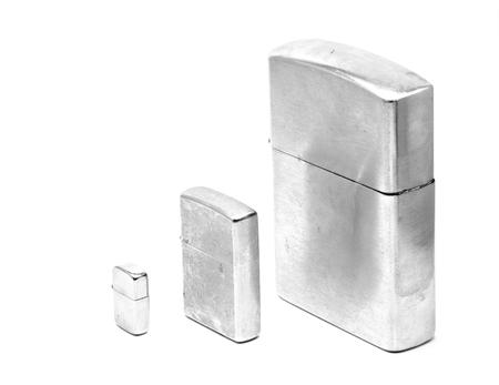 encendedores: Tres tamaños diferentes de encendedores metálicos con la tapa cerrada