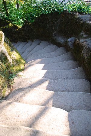 subiendo escaleras: Narrow stone steps going round with trees on the sideway Foto de archivo
