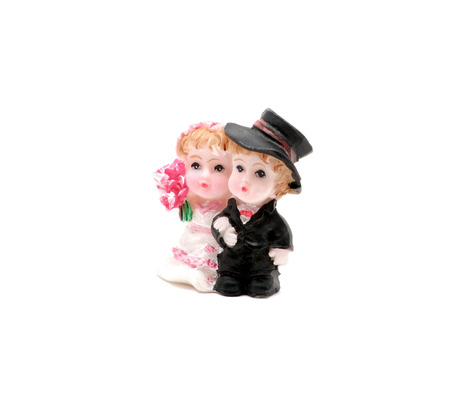 Isolated small figurine of newlywed couple in wedding outfits