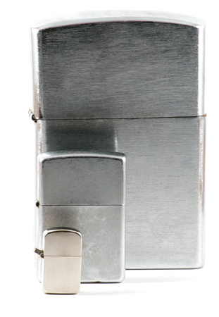 encendedores: Three different sizes of metallic lighters with cap closed over white
