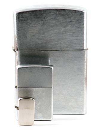 encendedores: Tres tamaños diferentes de encendedores metálicos cerrados con tapón de más de blanco Foto de archivo
