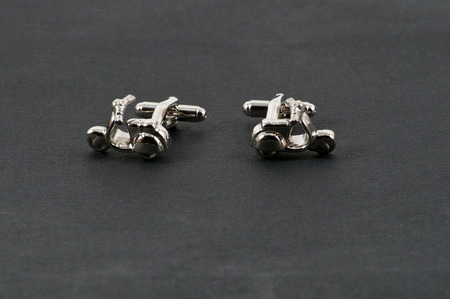 facing each other: Close up of cufflinks facing each other motorbikes over black