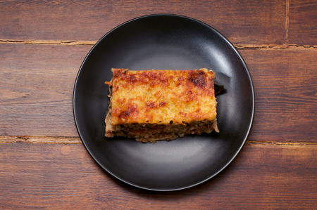 mouthwatering: Piece of lasagna on the black plate over wooden background in the center